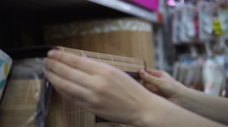 bamboo basket : A young woman in a blue checkered shirt chooses and buys a folding box for things in the supermarket in the department of household goods.