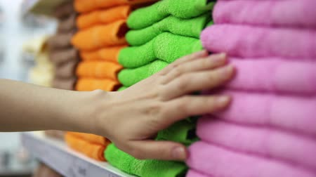 terry : A womans hand touches multi-colored terry towels, which are on the shelf in the textile department of the supermarket.