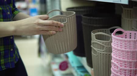 box set : A young woman in a blue checkered shirt chooses and buys plastic baskets for things in the supermarket in the department of household goods. Stock Footage