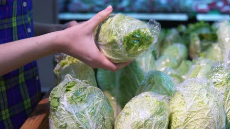 jarmuż : A young woman chooses and buys fresh chinese cabbage in a supermarket in the vegetable and fruit department.