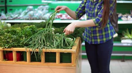 zöldségbolt : A young woman in a blue checkered shirt chooses and buys a green onion in the supermarket in the fresh food department.