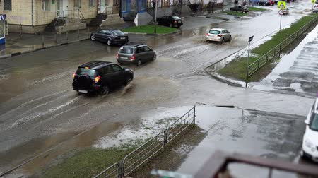 опасность : Flooded city road with big puddle of water spray from the wheels. Splash by car as it goes through flood water after heavy rains.