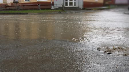 water hole : Water from heavy rain. Splash by cars when they pass through a large puddle near a storm sewer.