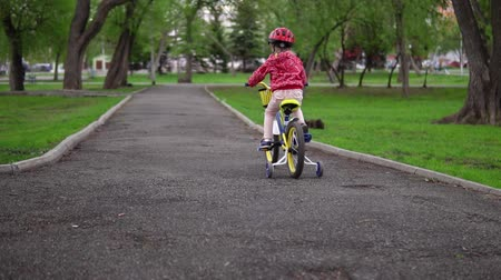 pokus : A happy little girl learns to ride a bicycle, she keeps her balance and speed on her bike in the park, slow-motion shooting.