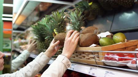sell : A young woman chooses and buys coconuts at the supermarket in the fresh food department.