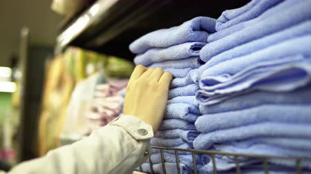 terry : A womans hand chooses and buys blue terry towels, which are on the shelf in the textile department of the supermarket.