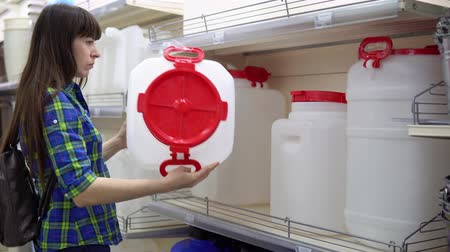 хранилище : A young woman chooses a large container for liquids in the supermarket. She wants to make a large supply of water or gasoline in her basement. Preparation for natural disasters and man-made disasters. Стоковые видеозаписи