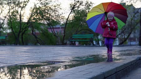 gumboots : A nice little girl with a colorful umbrella running through the puddles in the park at sunset. The child smiles and enjoys the fun, slow motion. Stock Footage
