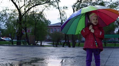 gumboots : A nice little girl in a red raincoat is standing by a puddle in the park at sunset. Drops of rain flow down a multi-colored umbrella. The child smiles and enjoys the fun.