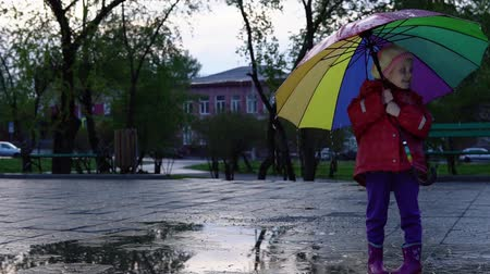 gumboots : A nice little girl in a red raincoat is standing by a puddle in the park at sunset. Drops of rain flow down a multi-colored umbrella. The child smiles and enjoys the fun, slow motion.