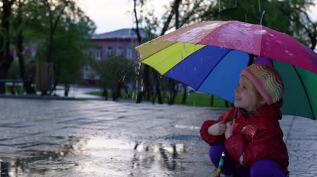 gumboots : A cute little girl is sitting by the puddle in the park at sunset. Drops of rain flow down a multi-colored umbrella. The child smiles and enjoys the fun, slow motion.