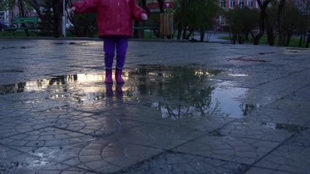 mateřská škola : A cute little girl in a red raincoat jumping over a puddle in the park at sunset. The child smiles and enjoys the fun.