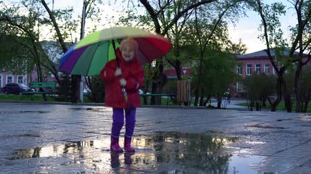 gumboots : A cute little girl with a colorful umbrella is jumping in the puddles in the park at sunset.