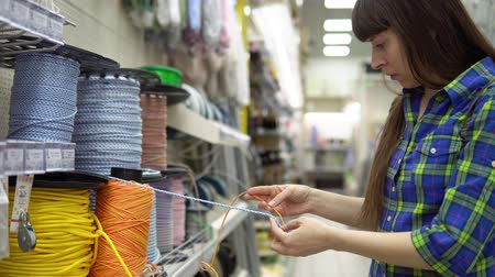 přadeno : A young woman in a blue checkered shirt chooses a solid multi-colored rope in a supermarket. Dostupné videozáznamy