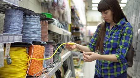 selecionando : A young woman in a blue checkered shirt chooses a solid multi-colored rope in a supermarket. Vídeos