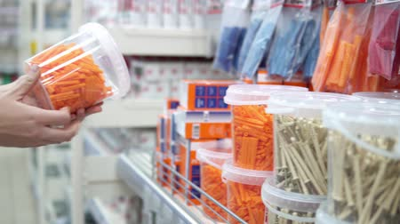 fasteners : A young woman chooses a transparent container with orange corrugated plastic plugs in the store. She is preparing for repair or construction. Stock Footage
