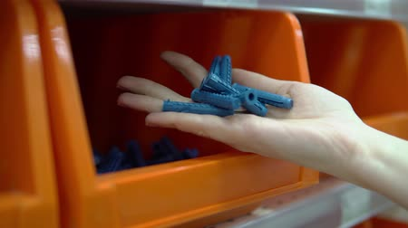fasteners : Close-up of a hand takes an orange container from a corrugated plastic plugs. Selection and purchase of building materials in the hypermarket.