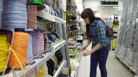 cadarço : A young woman in a blue checkered shirt chooses a solid rope in a supermarket.