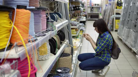 meada : A young woman in a blue checkered shirt chooses a solid multi-colored rope in a supermarket. Vídeos