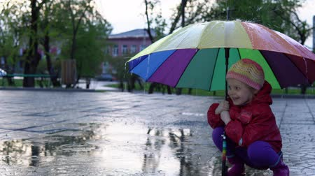 gumboots : A cute little girl is sitting by the puddle in the park at sunset. Drops of rain flow down a multi-colored umbrella. The child smiles and enjoys the fun.