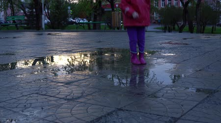 gumboots : A cute little girl in a red raincoat jumping over a puddle in the park at sunset. The child smiles and enjoys the fun.