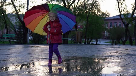 gumboots : A cute little girl with a colorful umbrella is jumping in the puddles in the park at sunset. The child smiles and enjoys the fun, slow motion.