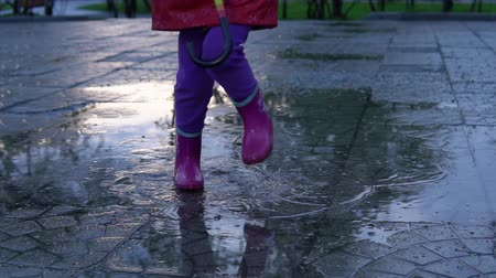 gumboots : A cute little girl in a red raincoat jumping over a puddle in the park at sunset. The child smiles and enjoys the fun, slow motion. Stock Footage