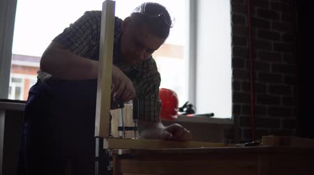 workman : Process of building a wooden table.
