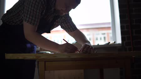 cabinetry : The process of building a wooden table, the carpenter, the right size for the part from the beam, a dolly shot Stock Footage