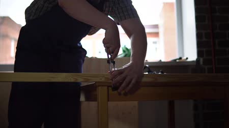cabinetry : The process of building a wooden table, the carpenter measures the right size for the part from the beam. The artisan fastens the wooden block to the table with a clamp, dolly shot. Stock Footage