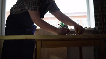 plywood : The process of building a wooden table, the carpenter, the right size for the part from the beam, dolly shot.
