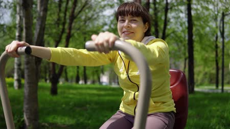 zasnoubený : Young attractive woman trains on stationary outdoor simulators in the summer day.