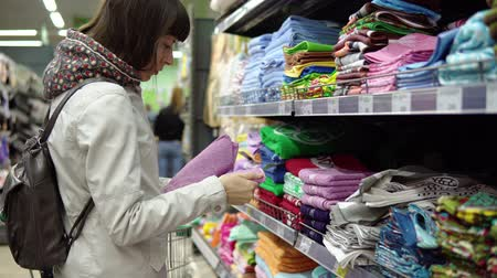 terry : Young brunette woman chooses and buys blue terry towels, which are on the shelf in the textile department of the supermarket. Stock Footage