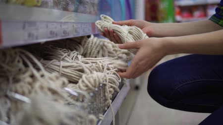přadeno : A young woman in a classic shirt chooses and buys a rope in the supermarket in the department of household goods.