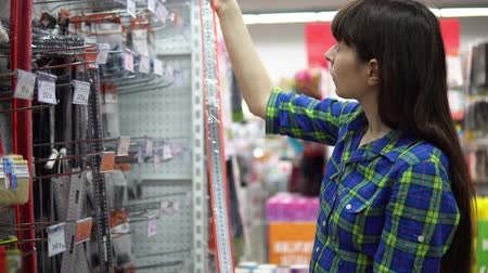 metrik : A young woman in a blue checkered shirt chooses and buys a large iron ruler with an angle in the supermarket in the building materials department.