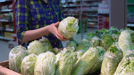 supermarket shelf : A young woman chooses and buys fresh chinese cabbage in a supermarket in the vegetable and fruit department.