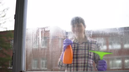 servant : Portrait of happy, young woman cleaning window at home on a brick building background.