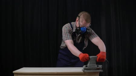 sander : The process of building a table, a male carpenter polishes a wooden part. He uses an industrial grinder and aligns the surface of the countertop. Stock Footage