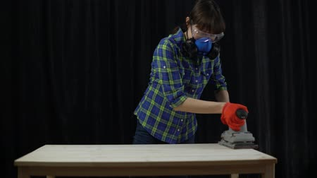 плотничные работы : The process of building a wooden table, a woman carpenter polishes a wooden part. It uses an industrial grinder and aligns the surface of the countertop.