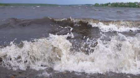 waste water : Dirty waves with white foam carry garbage to the shore after the storm, slowed down traffic, slow-motion.