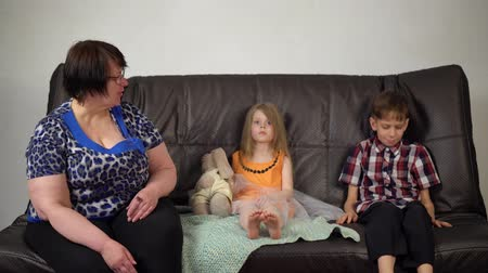 disobedient : Grandmother and grandchildren sit on a dark couch, an adult woman pronounce children for misconduct. Brother and sister upset.