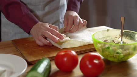 pita : The process of preparing doner, a young woman dressed in an apron in her kitchen wraps pita bread with sliced cucumbers, cabbage and chicken.