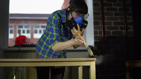 мастер на все руки : The process of building a wooden table, a woman carpenter smacks wood dust from the table top with a brush in the workshop, slow motion. Preparation of the product for coating with oil or varnish.