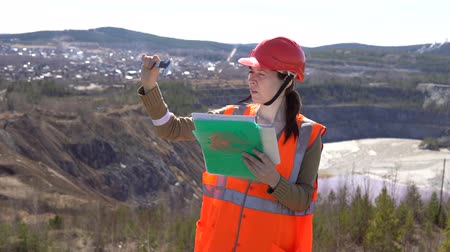 pedreira : A young woman checks documents against the background of an open-air career on a sunny day. She is wearing an orange vest and a protective helmet. Stock Footage
