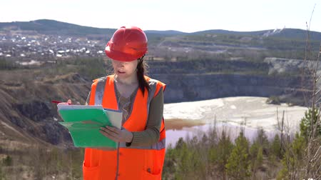 taş ocağı : A young woman checks documents against the background of an open-air career on a sunny day. She is wearing an orange vest and a protective helmet. Stok Video