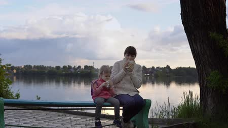 pita : A young mother and a small daughter eat doner kebab together on the street next to the pond, the water reflects the clouds and the opposite shore. Family shows thumbs up. Stock Footage