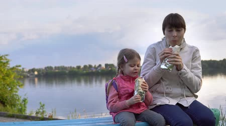 lavash : A young mother and a small daughter eat doner kebab together on the street next to the pond, the water reflects the clouds and the opposite shore. Family spend time together on the day off.