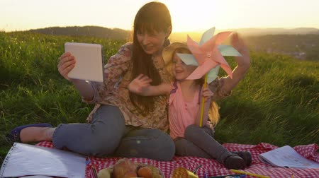 e book : Mother and daughter on a picnic on a mountain in the summer at sunset. The family together holds a day off in nature, using with electronic tablet and play with a pinwheel.