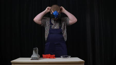 sander : The carpenter prepares to polish the table, the young man puts on a blue protective mask in the workshop on a black background.