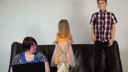 disobedient : Happy brother and sister jumping on the couch in the room. The grandmother sits next to the children and tries to work for the laptop, she asks grandchildren to stop the game, slow motion.